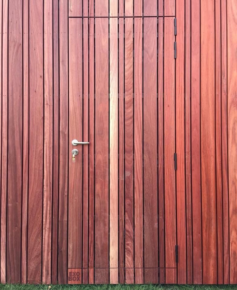 lasercut logo van exo box op houten tuinhuisje als maatwerk van ontwerp rik verhaest